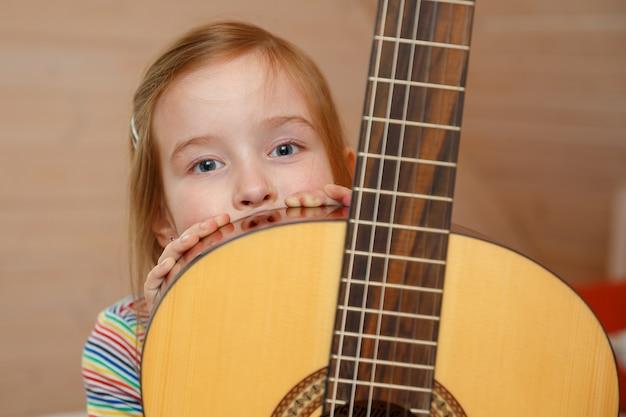 Klein meisje gluurt thuis achter een gitaarkoffer.