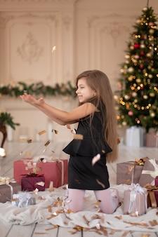 Klein meisje gooit confetti. kerstmagie. vrolijke momenten van een gelukkige jeugd.