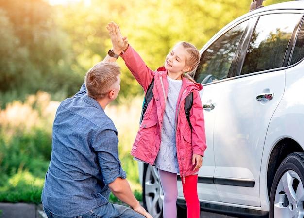 Klein meisje groet vader na school in de buurt van auto