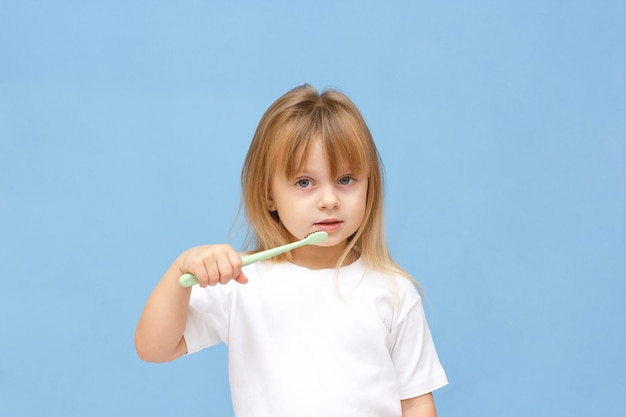 Klein meisje haar tanden poetsen en dragen op een blauwe achtergrond.