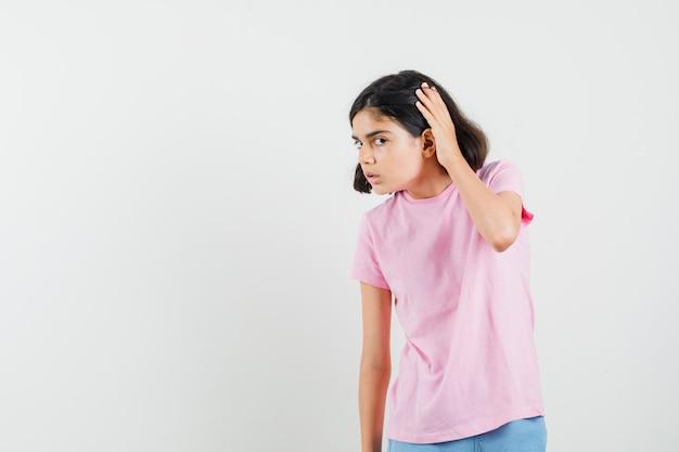Klein meisje hand in de buurt van oor in roze t-shirt, korte broek en op zoek nieuwsgierig. vooraanzicht.