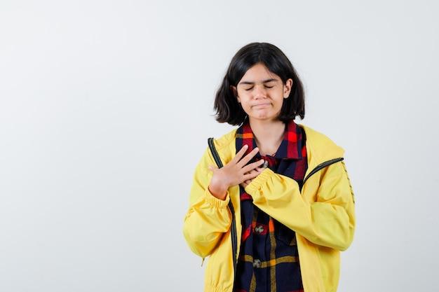 Klein meisje hand in hand op de borst in geruit overhemd, jas en ziet er hoopvol uit, vooraanzicht.