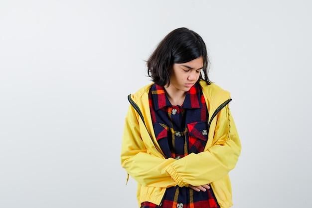 Klein meisje hand in hand op de buik in geruit hemd, jas en ziet er onwel uit, vooraanzicht.