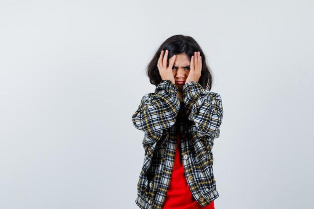 Klein meisje hand in hand op haar hoofd in shirt, jas en kijkt angstig, vooraanzicht.