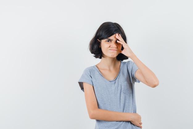 Klein meisje hand op hoofd in t-shirt houden en vergeetachtig, vooraanzicht op zoek.