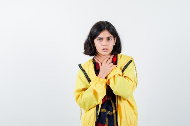 Klein meisje hand op keel in ingecheckte overhemd, jasje en onwel kijken