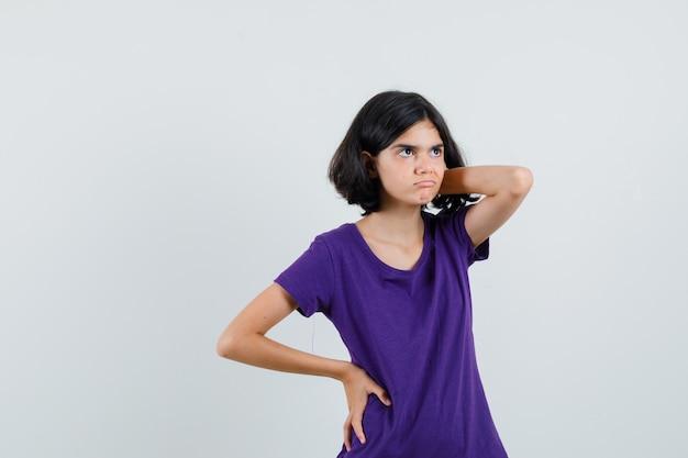 Klein meisje hand op nek in t-shirt en aarzelend op zoek,