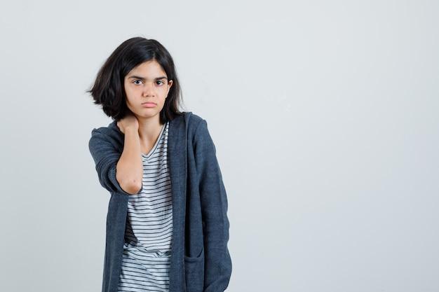 Klein meisje hand op nek in t-shirt, jas en op zoek verdrietig