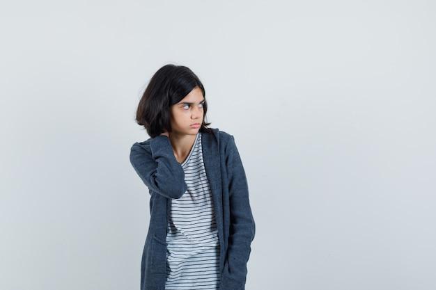 Klein meisje hand op nek in t-shirt, jasje en peinzend op zoek.