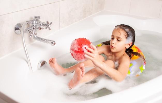 Klein meisje heeft plezier in de badkuip en speelt in de opblaasbare rode bal terwijl ze in de badkuip zit