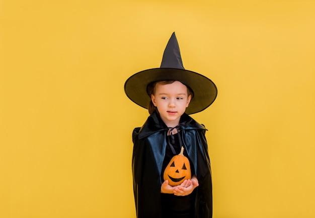 Klein meisje heks met een oranje pompoen met een gezicht staat en kijkt weg op een geel geïsoleerd