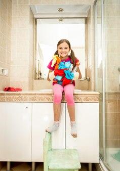 Klein meisje helpt met het schoonmaken van de badkamer poseren met reinigingsmiddelen