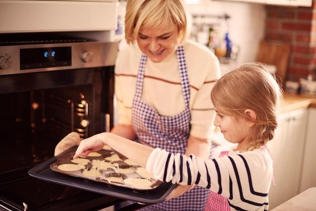 Klein meisje helpt oma tijdens het bakken