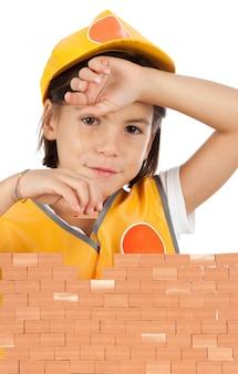Klein meisje het bouwen van een muur op wit wordt geïsoleerd