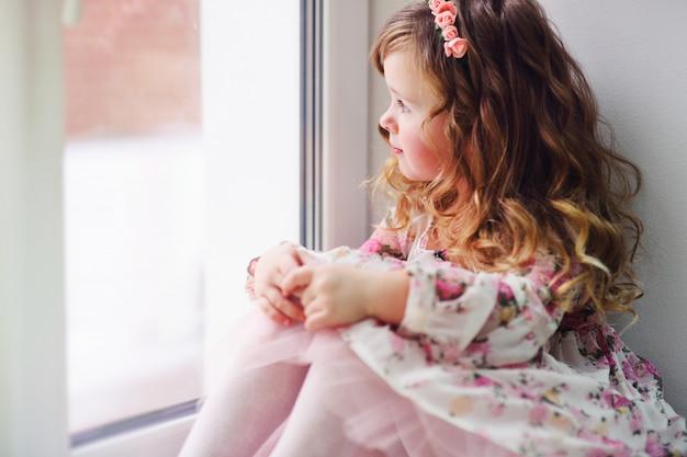 Klein meisje, het kind in een slimme jurk zit op de vensterbank, kijkt uit het raam en is verdrietig.