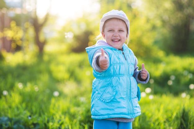 Klein meisje houdt de duim omhoog in een veld met groen gras en bloeiende tulpen bij zonsondergang