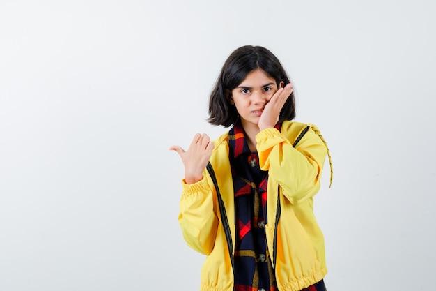 Klein meisje houdt de hand op de wang terwijl ze naar de linkerkant wijst met de duim in een geruit overhemd, jasje en er zelfverzekerd uitzien