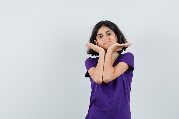 Klein meisje houdt de handpalmen onder de kin in een t-shirt en ziet er schattig uit,