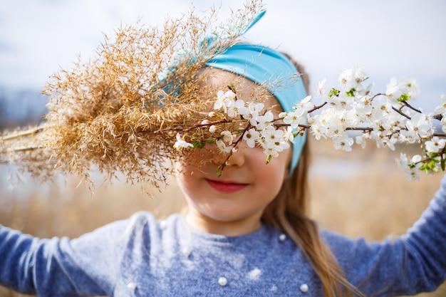 Klein meisje houdt droog riet en een tak met kleine witte bloemen in handen, zonnig lenteweer, glimlach en vreugde van het kind
