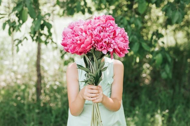 Klein meisje houdt een boeket roze pioenrozen in bloei in zijn handen en legt het over haar gezicht