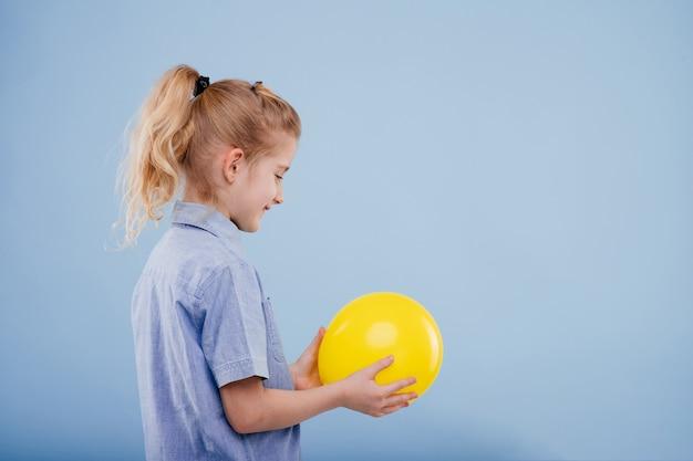 Klein meisje houdt een gele ballon vast met een glimlach. kijk naar de bal. profielweergave, geïsoleerd op een blauwe achtergrond, kopieer ruimte