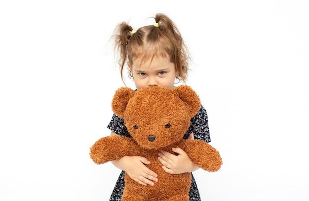 Klein meisje houdt een teddybeer geïsoleerd op wit en kijkt naar de camera met peinzende uitdrukking