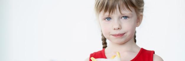 Klein meisje houdt frietjes in pakket in haar handen. onjuiste en ongezonde voeding bij kinderen concept