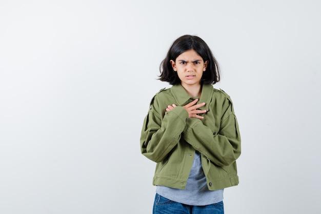 Klein meisje houdt gekruiste handen op de borst in jas, t-shirt, spijkerbroek en kijkt weemoedig, vooraanzicht.