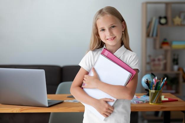 Klein meisje houdt haar boeken vast