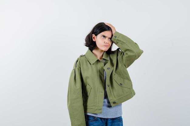 Klein meisje houdt hand op hoofd in jas, t-shirt, spijkerbroek en kijkt weemoedig. vooraanzicht.