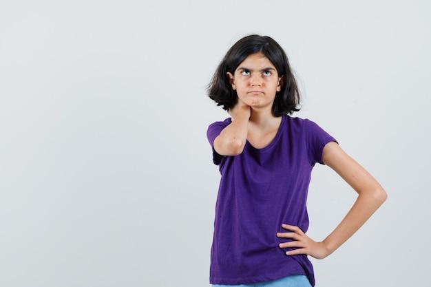 Klein meisje houdt hand op nek in t-shirt en kijkt besluiteloos,