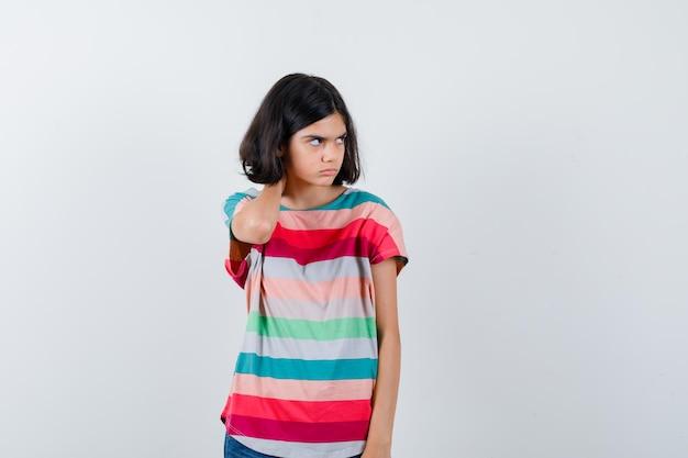 Klein meisje houdt hand op nek, kijkt weg in t-shirt en kijkt ontevreden, vooraanzicht.