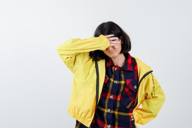 Klein meisje houdt hand op voorhoofd in geruit overhemd, jasje en kijkt weemoedig, vooraanzicht.
