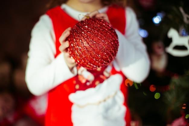 Klein meisje houdt rode kerstboom speelgoed in haar armen