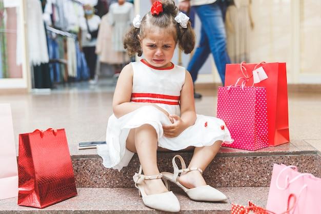 Klein meisje huilend in het winkelcentrum met gekleurde tassen