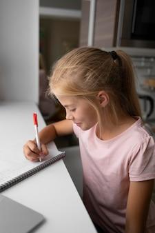 Klein meisje huiswerk thuis met laptop en notebook