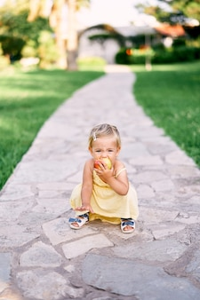 Klein meisje hurkt op een verhard pad in het park en knabbelt aan een appel