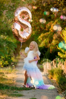 Klein meisje in avondjurk met ballonnen op een wandeling