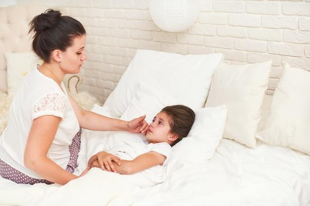 Klein meisje in bed liggen en wanhopig huilen, met koorts, is ziek