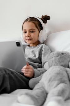 Klein meisje in bed met koptelefoon met behulp van tablet