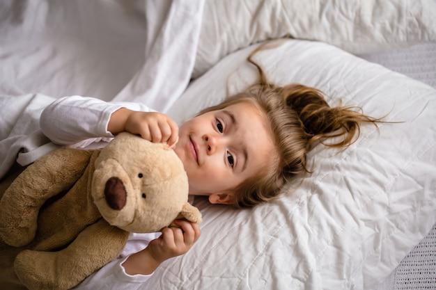 Klein meisje in bed met zacht stuk speelgoed de emoties van een kind