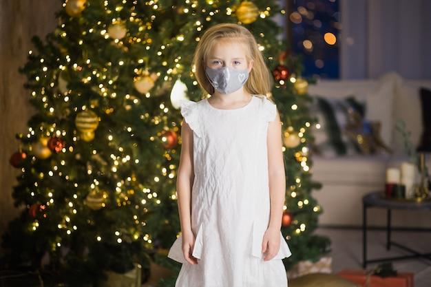 Klein meisje in beschermend masker en kerstmuts in ingerichte kerstkamer