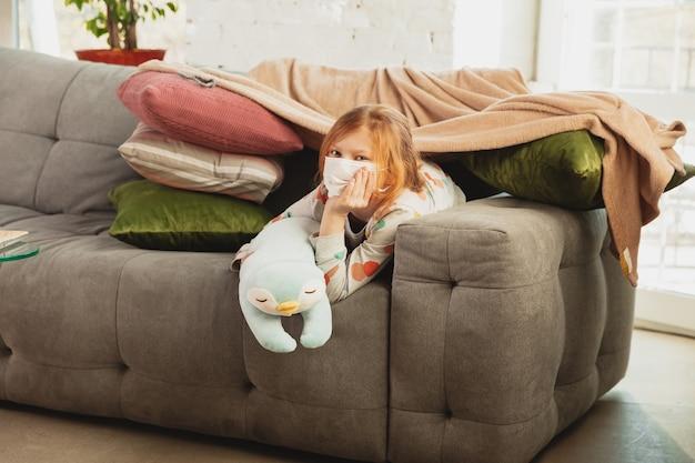 Klein meisje in beschermend masker thuis geïsoleerd met symptomen van het coronavirus