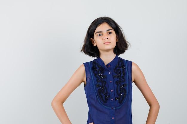 Klein meisje in blauwe blouse hand in hand op taille en op zoek naar ernstige, vooraanzicht.