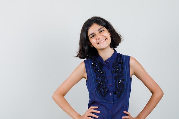 Klein meisje in blauwe blouse hand in hand op taille en op zoek vrolijk, vooraanzicht.