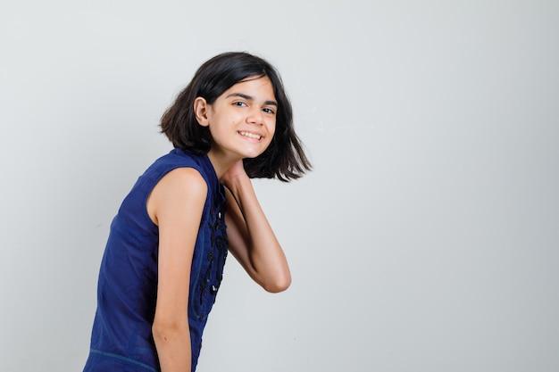 Klein meisje in blauwe blouse poseren met hand op nek en optimistisch op zoek.