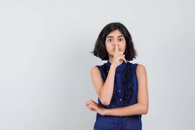 Klein meisje in blauwe blouse stilte gebaar tonen en voorzichtig kijken