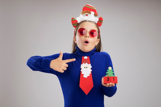 Klein meisje in blauwe coltrui dragen grappige kerst rand op hoofd houden speelgoed kubussen met gelukkig nieuwjaar datum op zoek verrast wijzend met wijsvinger naar kubussen permanent op witte achtergrond