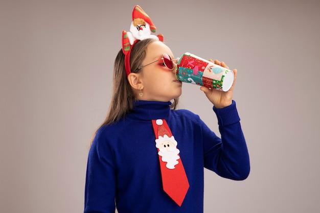 Klein meisje in blauwe coltrui met grappige kerstrand op het hoofd en drinkt uit een kleurrijke papieren beker die over een witte muur staat