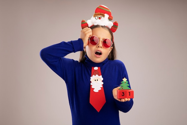 Klein meisje in blauwe coltrui met grappige kerstrand op het hoofd met speelgoedkubussen met gelukkig nieuwjaarsdatum verrast en verward over witte muur